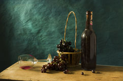 Still life Photography with Old red wine. On wooden table and blue grunge background Royalty Free Stock Photo