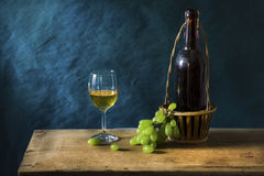 Still life Photography with Old white wine. Still life Photography with Old red wine on wooden table and blue grunge background Stock Photos