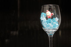 Still life Photography with Santa Claus in a glass of wine with ice in night time with dark background, Stock Photos