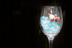 Still life Photography with Santa Claus in a glass of wine with ice in night time with dark background, Stock Image