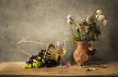 Still life Photography of shrivel. Still life Photography with wine, grape and flower on wooden table and dark grunge background Royalty Free Stock Photography