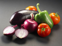 Still life photography of vegetables. Peppers, onions, tomatoes, eggplant Stock Photos