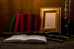 Still life of picture frame on wooden table with clarinet Royalty Free Stock Photography