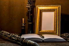 Still life of picture frame on wooden table with clarinet Stock Photos