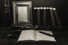 Still life of picture frame on wooden table with clarinet Royalty Free Stock Photo