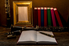Still life of picture frame on wooden table with clarinet Royalty Free Stock Image