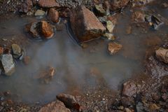 A still life picture of a puddle with rocks which shows peace and reflection royalty free stock images