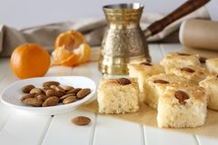 Still life Pieces Basbousa namoora traditional arabic semolina. Cake with almond nut and syrup, orange and cooper jezva. Copy space. Selective focus Royalty Free Stock Image