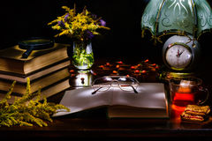 Still life of a pile of books,glasses,magnifier,vase with flowers,tea and biscuits,a lamp with a clock.Illuminated by the flashlig. Flowers in a vase,a stack of Stock Photo