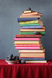 Still life with a pile of books and plums, a vertical shot. Stock Photos