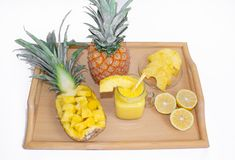Still life. Pineapple juice, cocktails with fresh pineapple for breakfast in the morning on a wooden tray, on a white background. Detox. For health and for royalty free stock photo