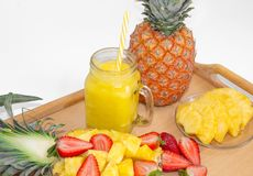 Still life. Pineapple juice, cocktails with fresh pineapple and fresh strawberries for breakfast in the morning, on a tray, on a w. Hite background. Close-up stock images