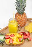 Still life. Pineapple juice, cocktails with fresh pineapple and fresh strawberries for breakfast in the morning, on a tray. On a white background. Close-up royalty free stock photo