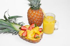 Still life. Pineapple juice, cocktails with fresh pineapple and fresh strawberries for breakfast in the morning, on a wooden table. Detox. For health and for royalty free stock image