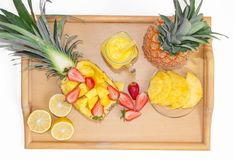 Still life. Pineapple juice, cocktails with fresh pineapple and fresh strawberries for breakfast in the morning, on a tray. On a white background. Close-up royalty free stock photos