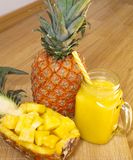 Still life. Pineapple juice, smoothies with fresh pineapple for breakfast in the morning on a wooden table. Detox. royalty free stock photo