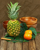 Still Life with Pineapple and Oranges on Wooden background. Closeup stock image