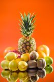 Still life pineapple and various fruits on orange background, vertical shot. Picture presents Still life pineapple and various fruits on orange background Stock Photography