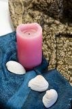 Still life of pink candle and see shells. On drapery Royalty Free Stock Images