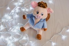Still life pink happy piglet and LED holiday garland on wooden background, happy new year.  stock image