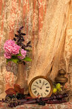 Still life. Pink hydrangea and violet basil bouquet in the vintage vase with antique clock and oil lamp Royalty Free Stock Image