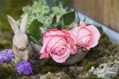 Still life with pink of rose and Rabbit ceramic plaster on moss Royalty Free Stock Photo