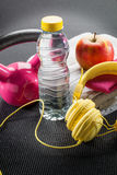 Still-life of pink weight lifting, earphones, towel and apple Stock Photos