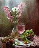 Still-life with pink wine and fruit and gladioluses. Still-life with pink wine, grapes, peaches, and a bouquet of gladioluses stock image