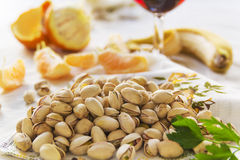 Still life of pistachios, peases of orange and a glass of wine Stock Photos