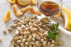 Still life of pistachios, peases of orange and a glass of wiskey Stock Photography