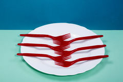 Still Life with a plastic fork and a plate on a colored. Background Stock Photos