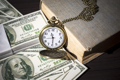 Still life of pocket watch on bills and old book Royalty Free Stock Photography