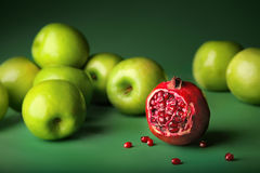 Still-life of pomegranate with apples. Still-life of pomegranate with green apples on darkly green background, different concepts - red pomegranate before green Royalty Free Stock Image