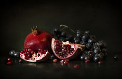 Still life of pomegranate and grapes. Still life with a picture of pomegranate and black grapes in a dark room Stock Photography