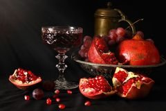 Still life with pomegranates, grapes and a glass of wine. Artistic still life with pomegranates, grapes and a glass of wine in the style of the old Dutch artists Royalty Free Stock Image