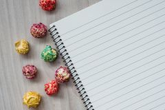 Still life of popcorn and a notepad are located on a wooden background. Top view. stock photos