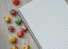 Still life of popcorn and a notepad are located on a wooden background. Top view. royalty free stock photos
