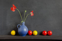 Still-life with poppy and colorful balls Royalty Free Stock Images