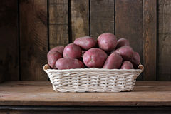 Still life with potatoes in a basket. Vegetables close up Royalty Free Stock Image