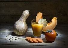 Still life with pumpkin juice. Pumpkin, persimmon, sliced carrots and a slice of lemon Stock Photography