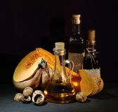 Still life; pumpkin, walnut, bottled oil on a dark background stock image