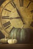 Still life of pumpkins and old clock stock photos