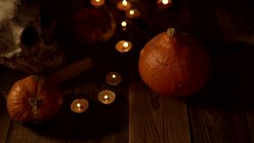 Still life of pumpkins and skulls on a wooden table when the candles go out