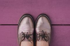Still life in purple color stylish women`s leather shoes with laces on a purple wooden board