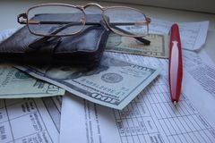 A still-life with a purse, a pen, glasses, receipts, calculations, money, dollars stock image