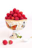 Still life with raspberry berries. Still life with raspberries in a vase. A photo in a light key. Raspberries in the vase and a couple of berries on the table Royalty Free Stock Image