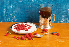 Still life. Raspberry with sour cream and a glass of tea Stock Photography