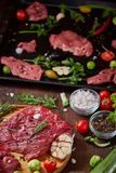 Still life of raw beef meat with vegetables on wooden plate over vintage background, top view, selective focus. Still life of raw beef meat with tomatoes, garlic Royalty Free Stock Photos