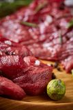 Still life of raw beef meat with vegetables on wooden plate over vintage background, top view, selective focus. Still life of raw beef meat with tomatoes, garlic Stock Photos