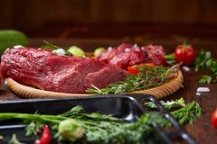 Still life of raw beef meat with vegetables on wooden plate over vintage background, top view, selective focus. Still life of raw beef meat with tomatoes, garlic Stock Images